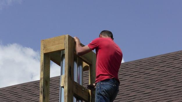 男は煙突を建てている屋根の煙突の建設と断熱