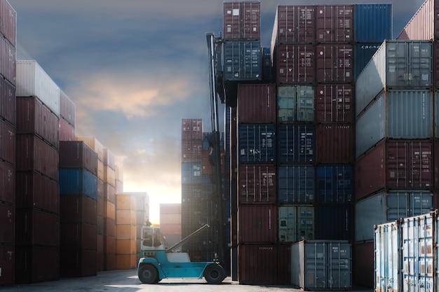 配送ヤードでフォークリフトトラック持ち上がる貨物コンテナー