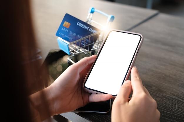 クレジットカードとお金で空白のスマートフォンを使用して女性のクローズアップ