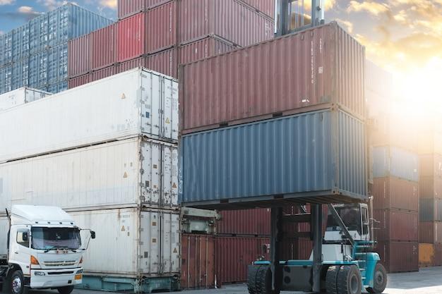 出荷ヤードの貨物コンテナーを持ち上げるフォークリフト