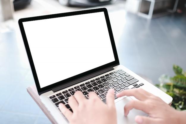 Изображение модель-макета женщины держа пустой мобильный телефон пока использующ компьтер-книжку с пустым экраном на таблице в кафе.