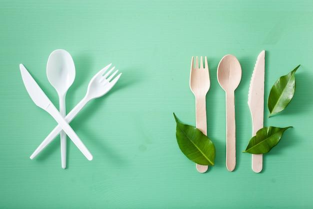 有害なプラスチック製カトラリーと環境に優しい木製カトラリー。プラスチック無料コンセプト