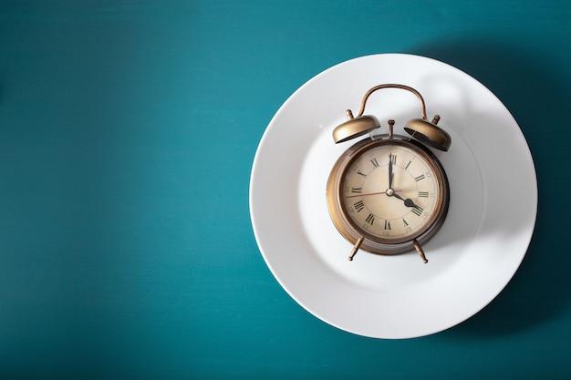 断続的な断食、ケトン食、減量の概念。プレート上の目覚し時計