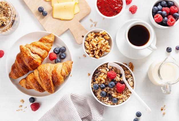 グラノーラ、ベリー、ナッツ、クロワッサン、ジャム、チョコレートスプレッド、コーヒーと健康的な朝食。上面図