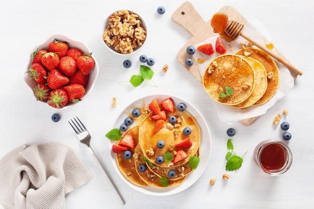 ブルーベリーイチゴ蜂蜜とナッツの朝食のパンケーキ
