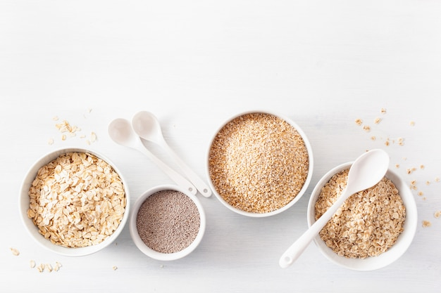 Вариаты из сырых злаков на завтрак. хлопья овсяные и стальные порезанные, ячмень, семена чиа. полезные ингредиенты