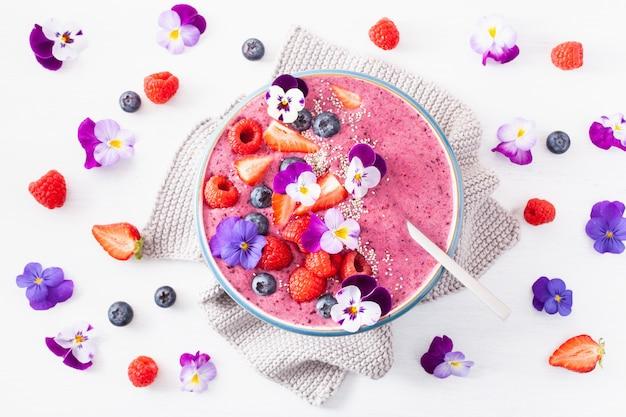 健康的な夏のベリースムージーボウル、花とチアシード