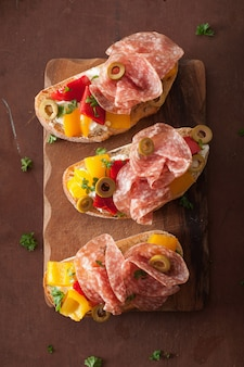 Брускетта с салями с жареным перцем, козий сыр, оливки