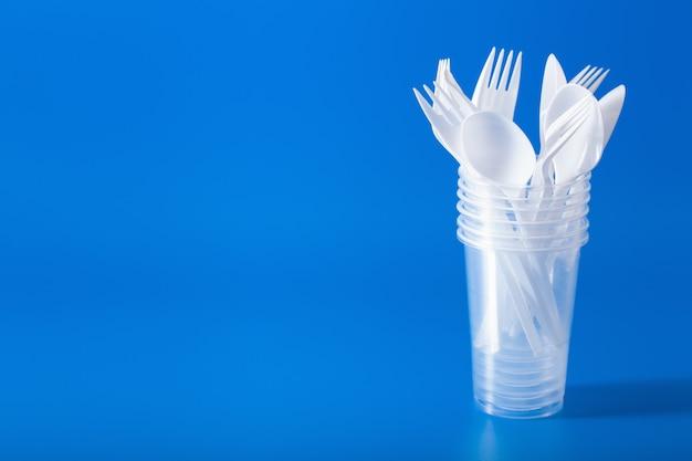 使い捨てのプラスチックカップ、フォーク、スプーン。プラスチック、プラスチック廃棄物のリサイクルの概念