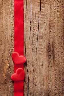 赤いハートとリボンフレームの木製の背景