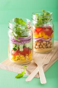 石工の瓶に健康的な野菜ひよこ豆のサラダ