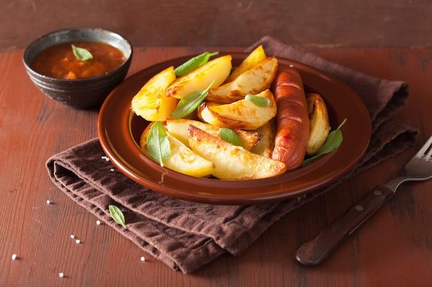 Запеченные картофельные дольки и колбаса на коричневом деревенском столе