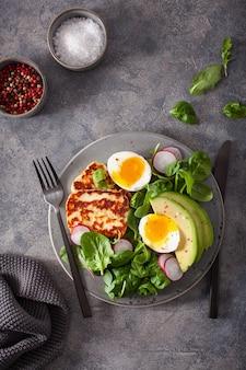 健康的なケトパレオダイエットの朝食:ゆで卵、アボカド、ハルーミチーズ、サラダの葉