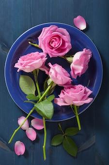 暗い青色の背景にピンクのバラの花