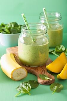 ガラスの瓶にほうれん草のマンゴーバナナと健康的な緑のスムージー
