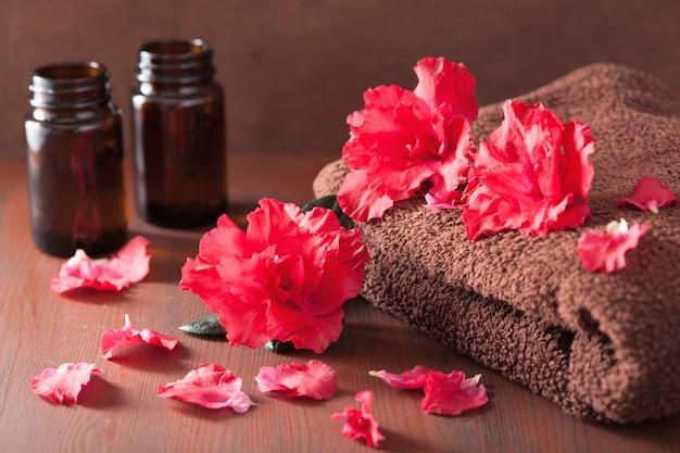 Спа ванная комната с эфирным маслом цветов азалии на темном деревенском столе