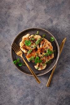 カリフラワーステーキとハーブソースとスパイス。植物ベースの肉代用品
