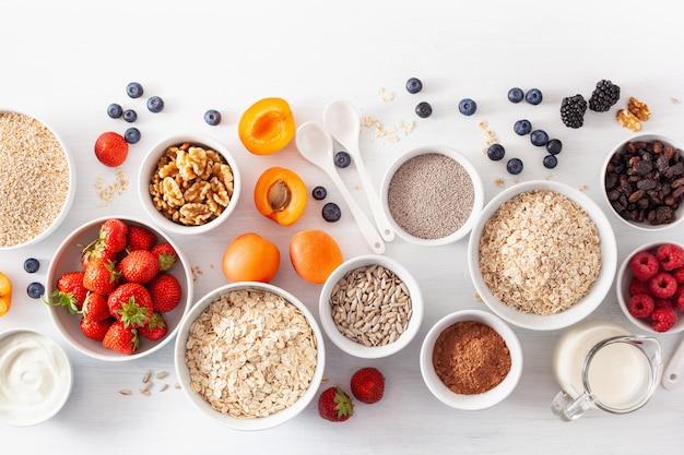 Вариаты из сырых злаков, фруктов и орехов на завтрак. хлопья овсяные и стальные порезанные, ячмень, орех, чиа, абрикос, клубника. полезные ингредиенты