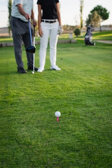 Мяч для гольфа, опираясь на тройник с двумя игроками не в фокусе в фоновом режиме. тройник на поле для гольфа.