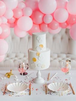 ホリデーパーティーのケーキ。子供のための明るい色のテーブルセッティング、エレガントな紙皿、金色のカトラリーグラス。女の子の誕生日のコンセプトです。ピンクの風船の装飾