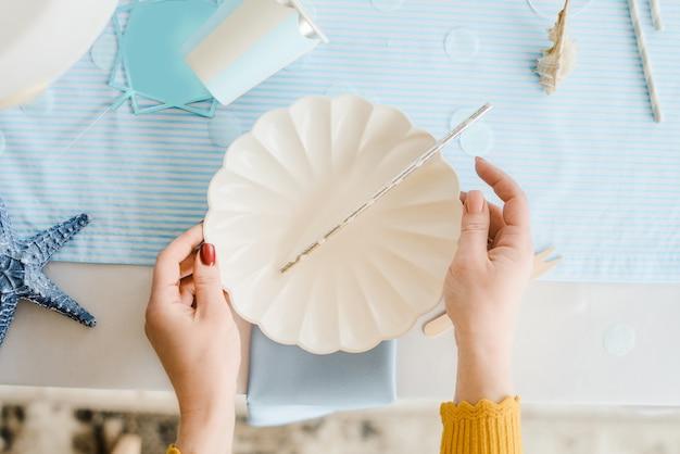 デコレータの手。誕生日やベビーシャワーのパーティーのための青と白の色で女性サービングテーブル。クローズアップ、トップビュー