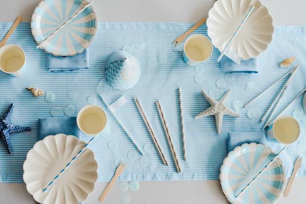 スカイブルーと白の色で子供や女の子のパーティーのために準備された誕生日テーブルの上の紙皿。海のスタイル。男の子のシャワー。トップビュー、フラットレイアウト