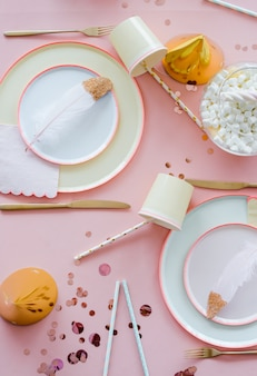 ピンクのテーブルクロス、紙のカラフルな料理、カップ、黄金のカトラリーとパステルカラーのパーティーテーブルの設定。女の子の装飾のお誕生日おめでとう。上面図