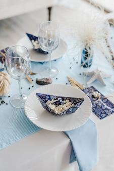 海スタイルのパーティーテーブルの設定。エレガントな白いお皿、グラス、ブルーカラー。マシュマロと紙の船。誕生日やベビーシャワーの少年のコンセプトです。