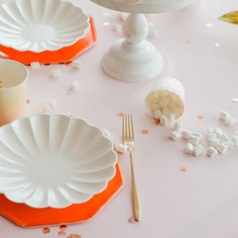 黄金のカトラリーとスタイリッシュな白いお皿、女の子のための準備された誕生日テーブルにカクテルストローと紙コップ。ピンク、白、金、赤の色のパーティー。マシュマロ