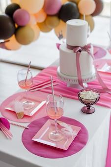 ピンク色のお祝いテーブルセッティング、白いお皿、ドリンク用グラス。カラフルな風船の装飾。ベビーシャワー、誕生日、または女の子のパーティー。