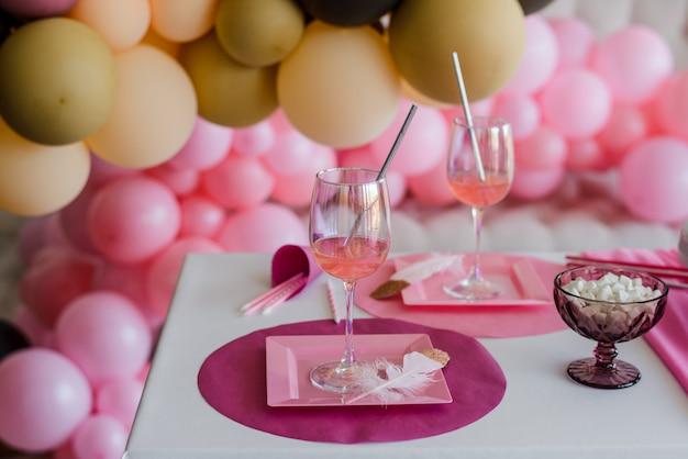 ピンク色のお祝いテーブルの設定、白いお皿、カクテルスティック付きグラス。カラフルな風船の装飾。誕生日、ベビーシャワー、女の子のパーティー。