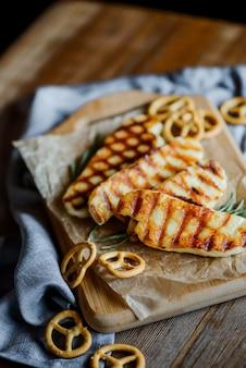 Жареный сыр халлуми с розмарином на деревянной разделочной доске на деревянный стол с небольшими кренделями