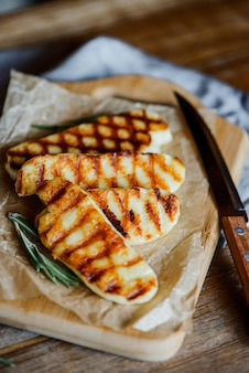 Жареный сыр халлуми с розмарином на деревянной разделочной доске на деревянный стол с деревянным ножом