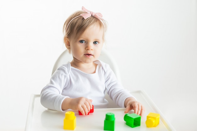 カラフルなおもちゃのブロックで遊ぶかわいい女の子。小さな子供が自宅でタワーを構築します。幼児のための教育玩具。幼児の子供のための建設ブロック。