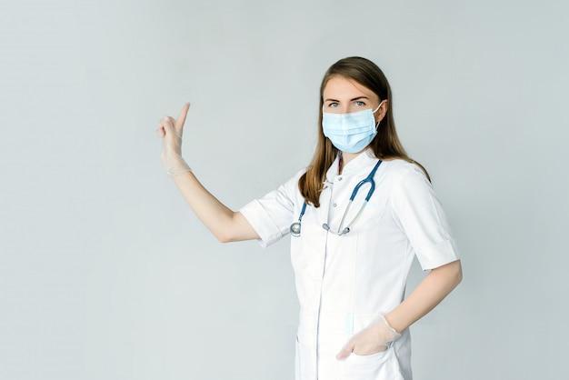 Мужской доктор человек в перчатках маска белый медицинское платье стерильные, изолированные на синем фоне. указательный палец вверх