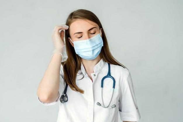 医療マスクとキャップで疲れている女性医師は灰色で分離された頭痛