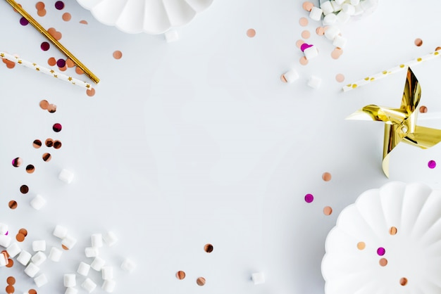 ホワイト、ゴールド、ピンクのデコレーション、キャンディー、スティック、皿、紙吹雪で作られたフレーム。フラット横たわっていた、トップビュー