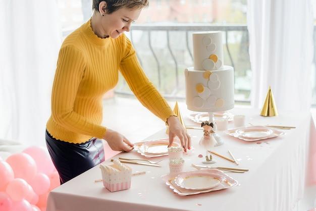 パステルカラーのパーティーテーブルの近くのデコレータ。ピンクのテーブルクロス、紙のカラフルな料理、カップ、金色のカトラリー。女の子の誕生日パーティーの装飾、お祝いキャップ。
