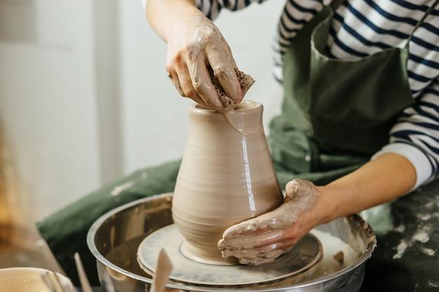 ろくろで土鍋を作る陶工の手。ワークショップでの陶器と陶器。