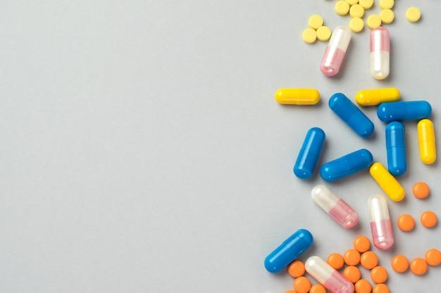 カラフルな錠剤やカプセル、コピースペースと灰色の背景上の薬。健康と投薬の概念。上面図。