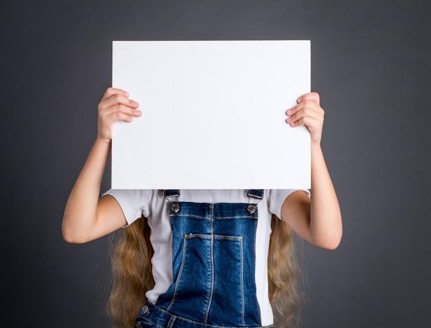 Девушка держа белую пустую доску знака на серой предпосылке.