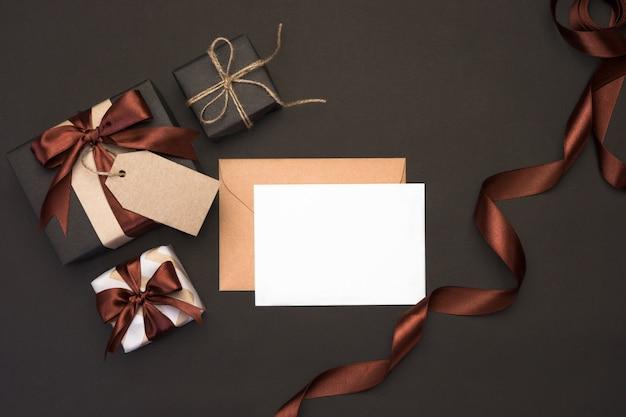 Подарочные коробки, завернутые в крафт-бумагу с коричневой лентой и лук на черном столе. подарки для мужчин концепции. открытка на день отца, праздничный декор