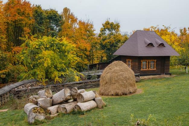 素朴なスタイルの小さな田舎の家の背景に干し草と大きな丸太。暖かい秋