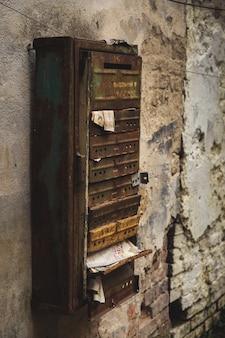 織り目加工の壁に古い金属のメールボックス