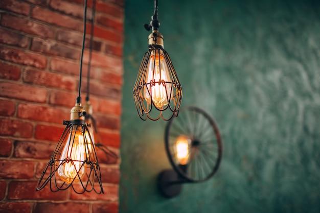 レンガの壁にレトロなランプ。白熱電球。スチール装飾ランプ。モダンなランプ。スチームパンクランプ