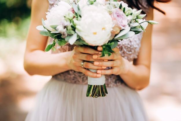 ウェディングブーケを持って優しい花嫁。牡丹の花束と自然の花嫁。