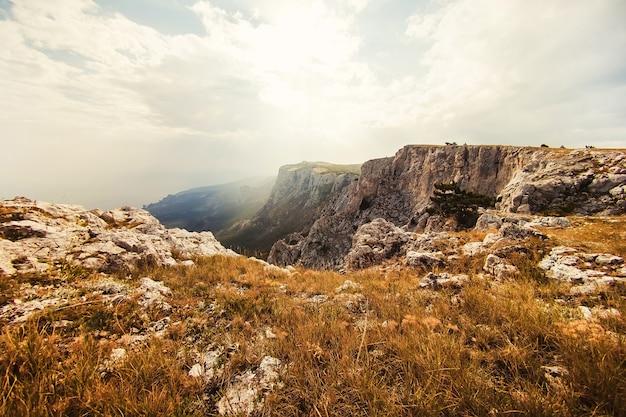 山を背景に足の観光客。太陽の下で山の風景。強大な山。山から海への眺め。