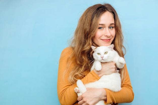 Молодая женщина держит в руках белый кот.