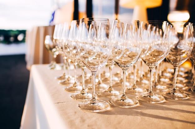 Много пустых бокалов шампанского заделывают. стеклянные бокалы на белом столе. пустой хрустальный бокал. стеклянный кубок на высокой ноге.