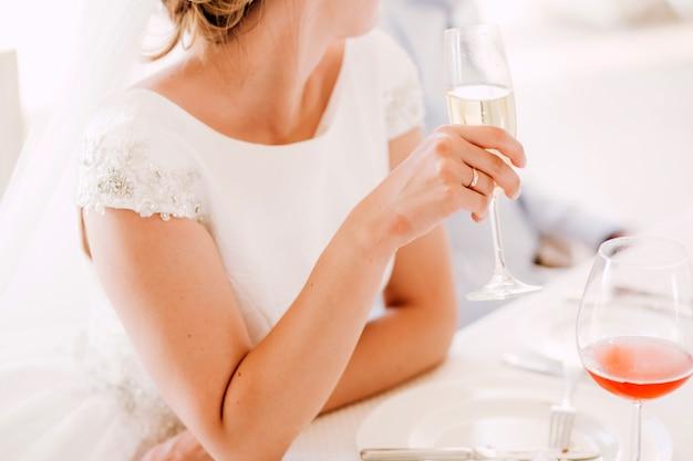 スイミングプールでの結婚式のためのテーブルの設定。白いテーブルクロスが付いた丸テーブル